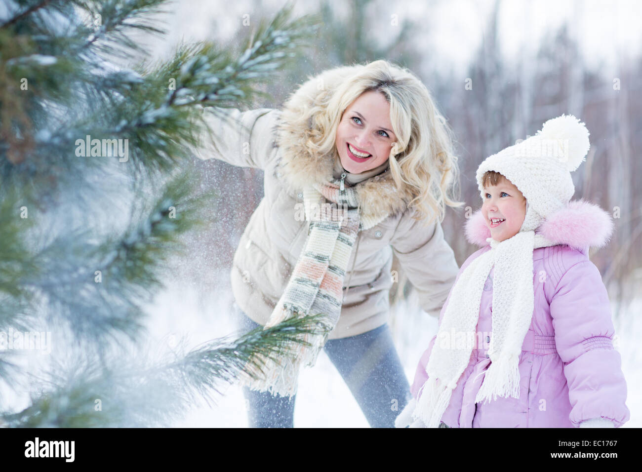 Happy parent and child playing with snow in winter outdoor - Stock Image
