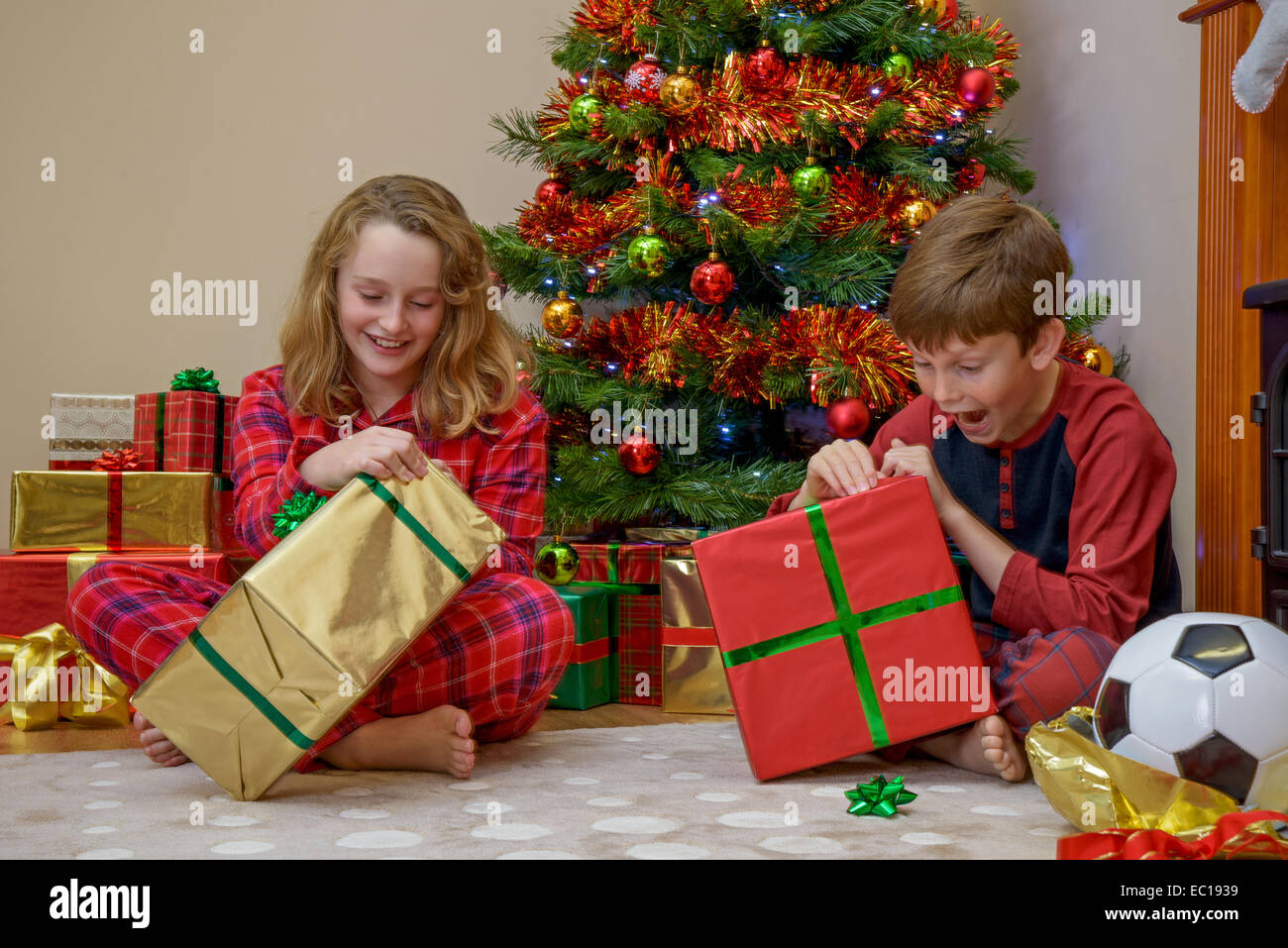 Two children, a boy and a girl, opening their presents on Christmas morning. - Stock Image