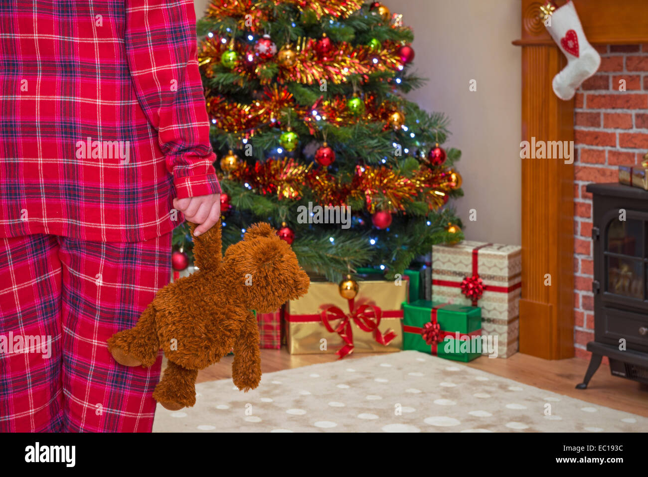 A little girl holding her teddy bear on Christmas morning, gift wrapped presents under the tree and a stocking over - Stock Image