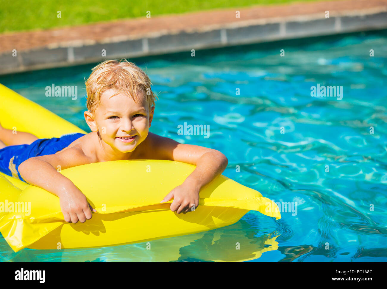 Happy Young Boy Floating in Swimming Pool on Raft Stock Photo