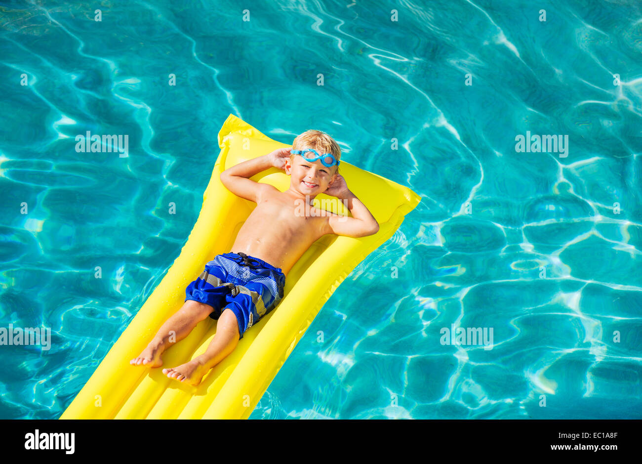 Young Boy Relaxing and Having Fun in Swimming Pool on Yellow Raft. Summer Vacation Fun. Relaxing Lifestyle Concept. - Stock Image