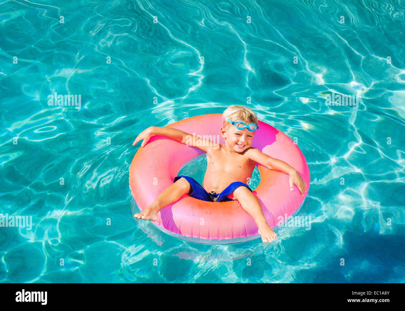 Young Kid Having Fun in the Swimming Pool On Inner Tube Raft. Summer Vacation Fun. - Stock Image