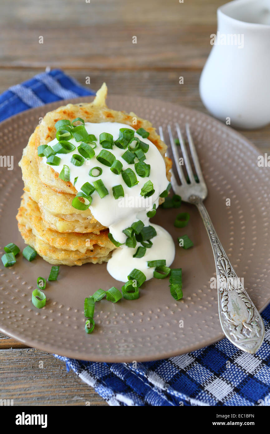Potato pancakes with sour cream and green onions on a plate, on wooden boards - Stock Image