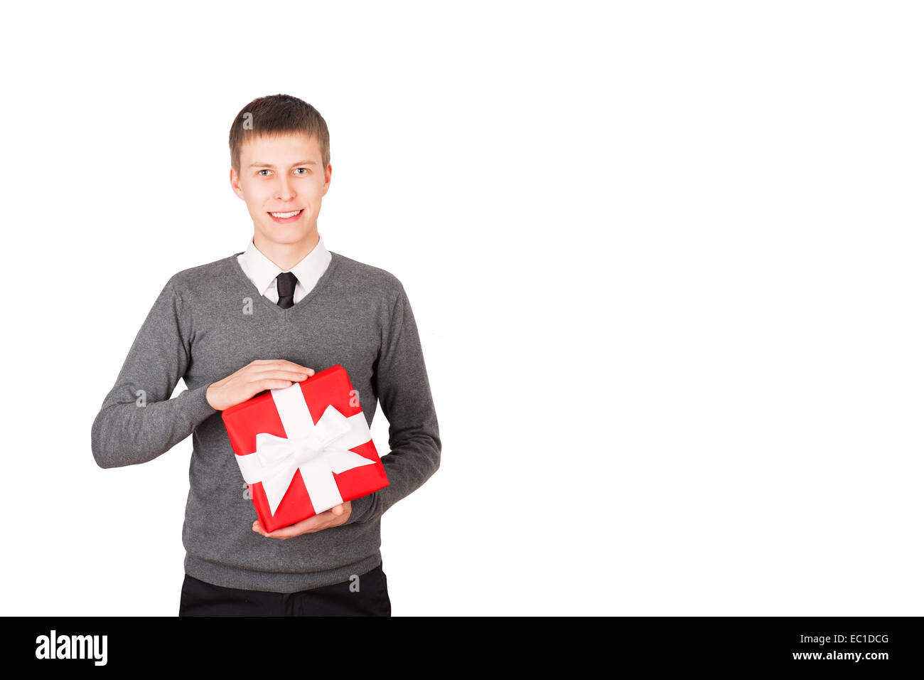 Young man with a christmas present in red packaging, isolated on white - Stock Image