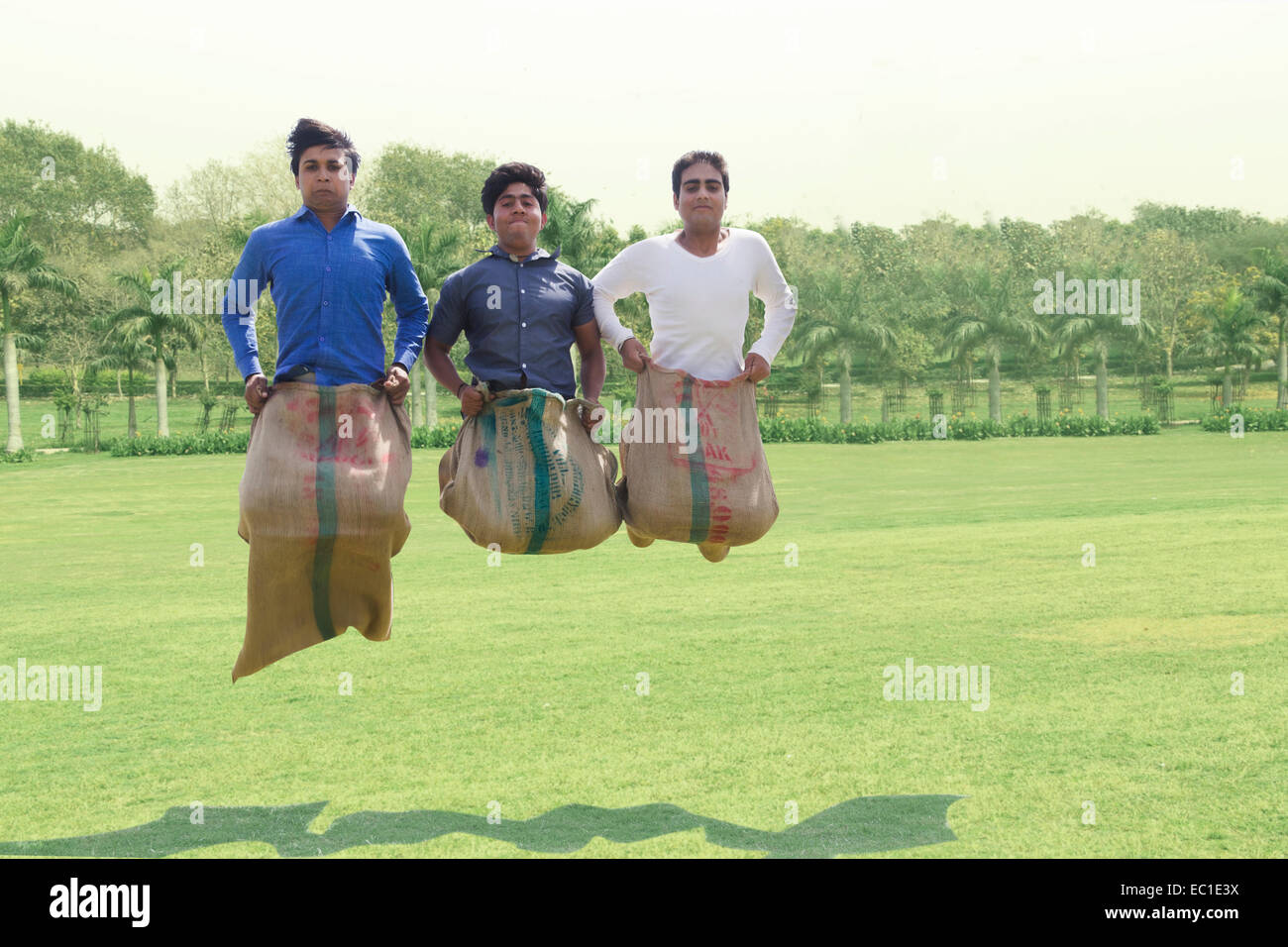 4 indian friends park playing Sack Race - Stock Image