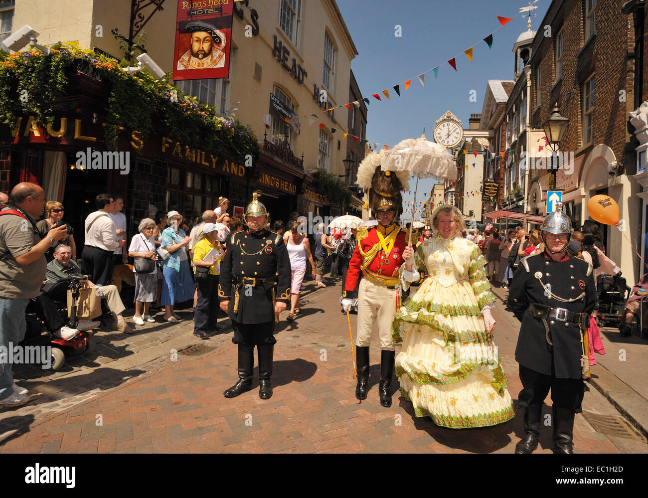 Dickens Festival grand parade, Rochester, Kent. Lady in red dress with officer, on Rochester high Street beneath Stock Photo