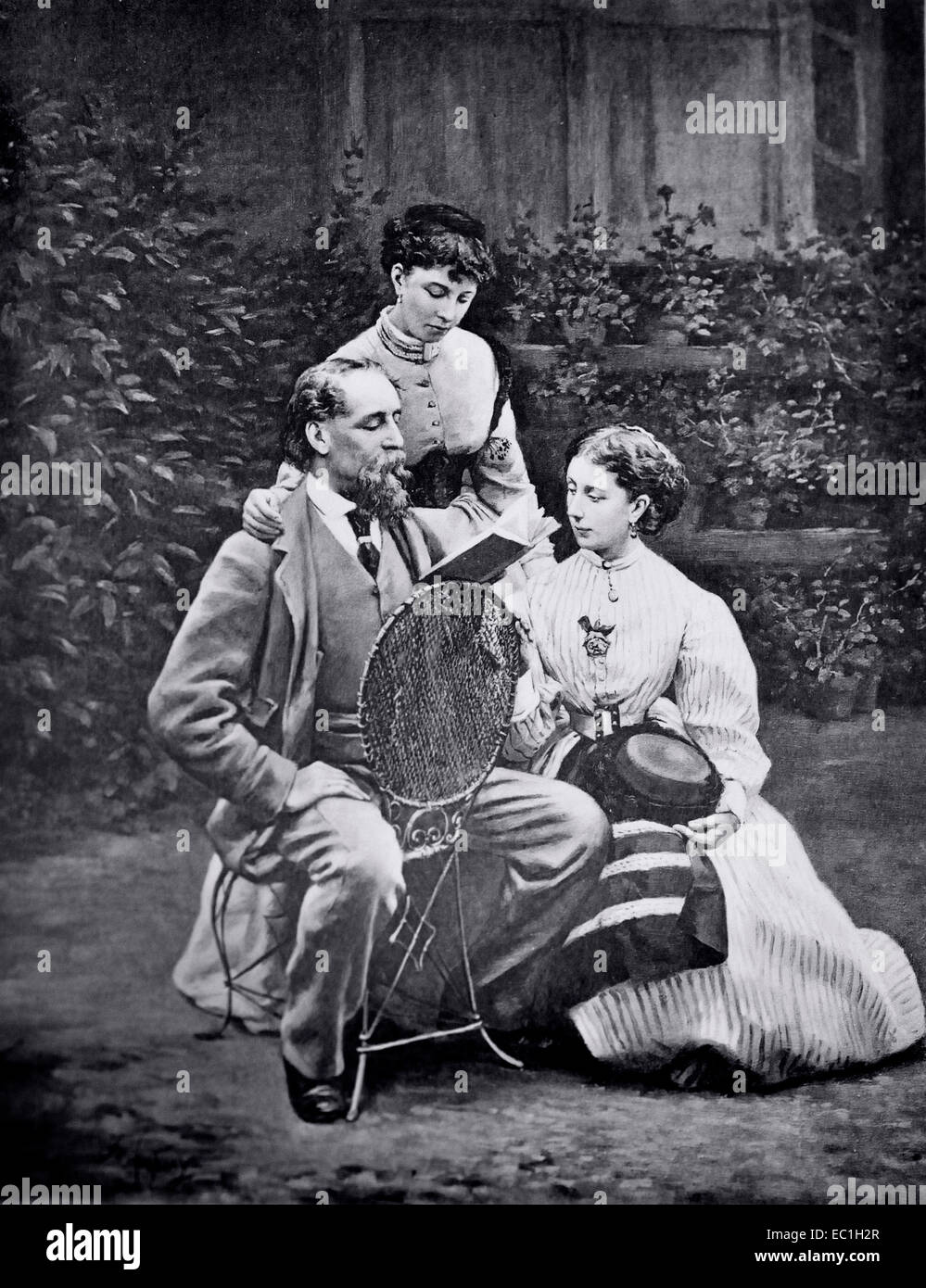 Photo of Charles Dickens reading to his daughters Mamie and Katey on the front lawn his home at Gad's Hill, Higham. - Stock Image