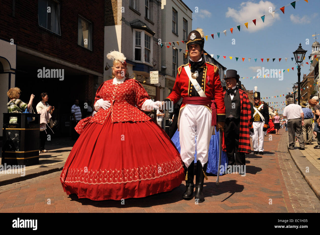 Dickens Festival grand parade, Rochester, Kent. Lady in red dress with officer, Rochester High Street. Novelist - Stock Image