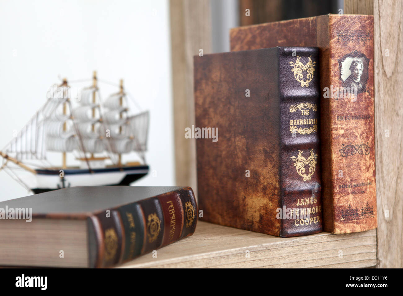 Old rare leatherbound books on a bookshelf with a model of a tall ship - Stock Image