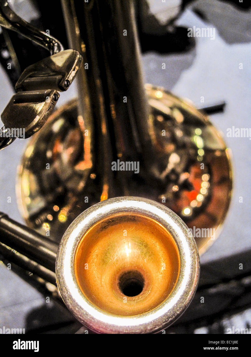 Mouthpiece, tenor trombone.  The trombone is resting on a stand. - Stock Image
