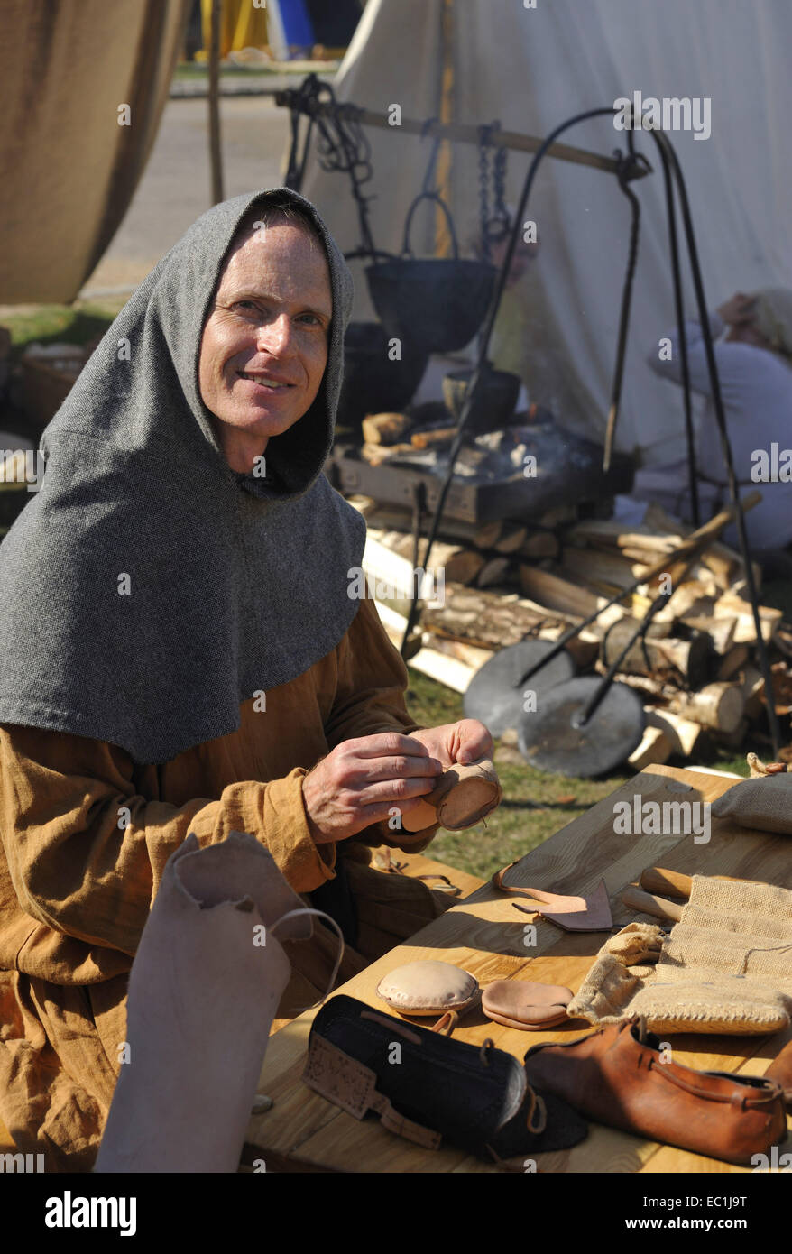 Mediaeval shoe making. Reconstruction (outside Rochester Castle, Kent) of leather preparation (over wood fire) and - Stock Image