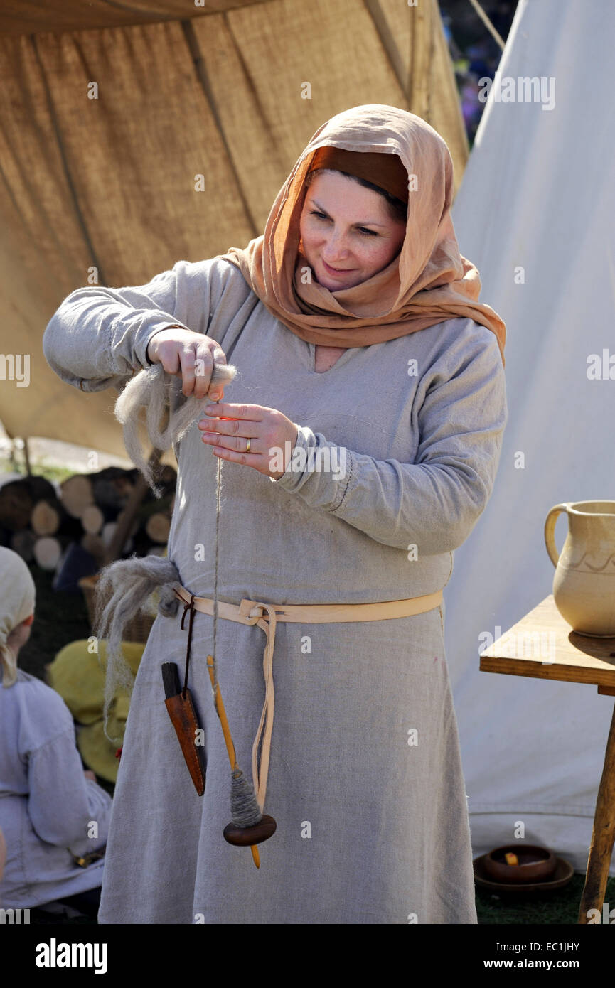 Mediaeval wool spinner. Woman spinning wool using a drop spindle and distaff. Reconstruction (outside Rochester - Stock Image