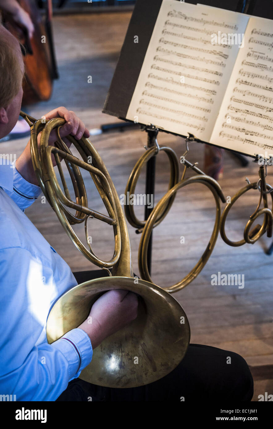 Classical natural horn, with crooks hanging from music stand. The crooks are used to change the pitch, scale and - Stock Image