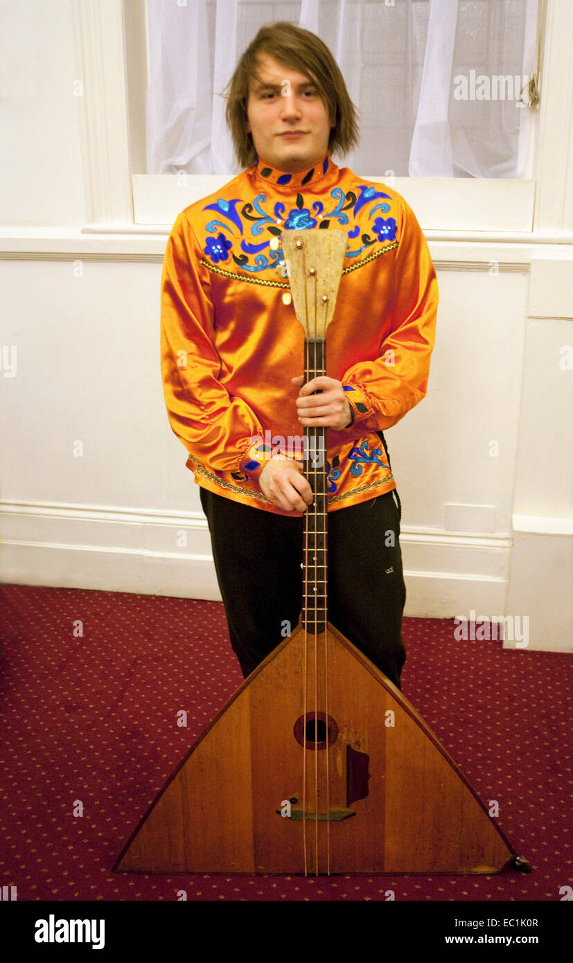 Bass balalaika. The balalaika  is a Russian folk stringed musical instrument with a characteristic triangular body - Stock Image