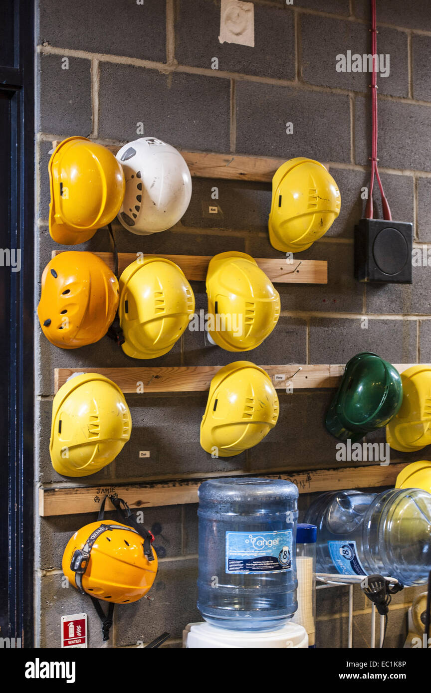 Hard hats backstage on theatre wall, with fresh water fountain, for the use of stage crew. In the new Milton Keynes - Stock Image