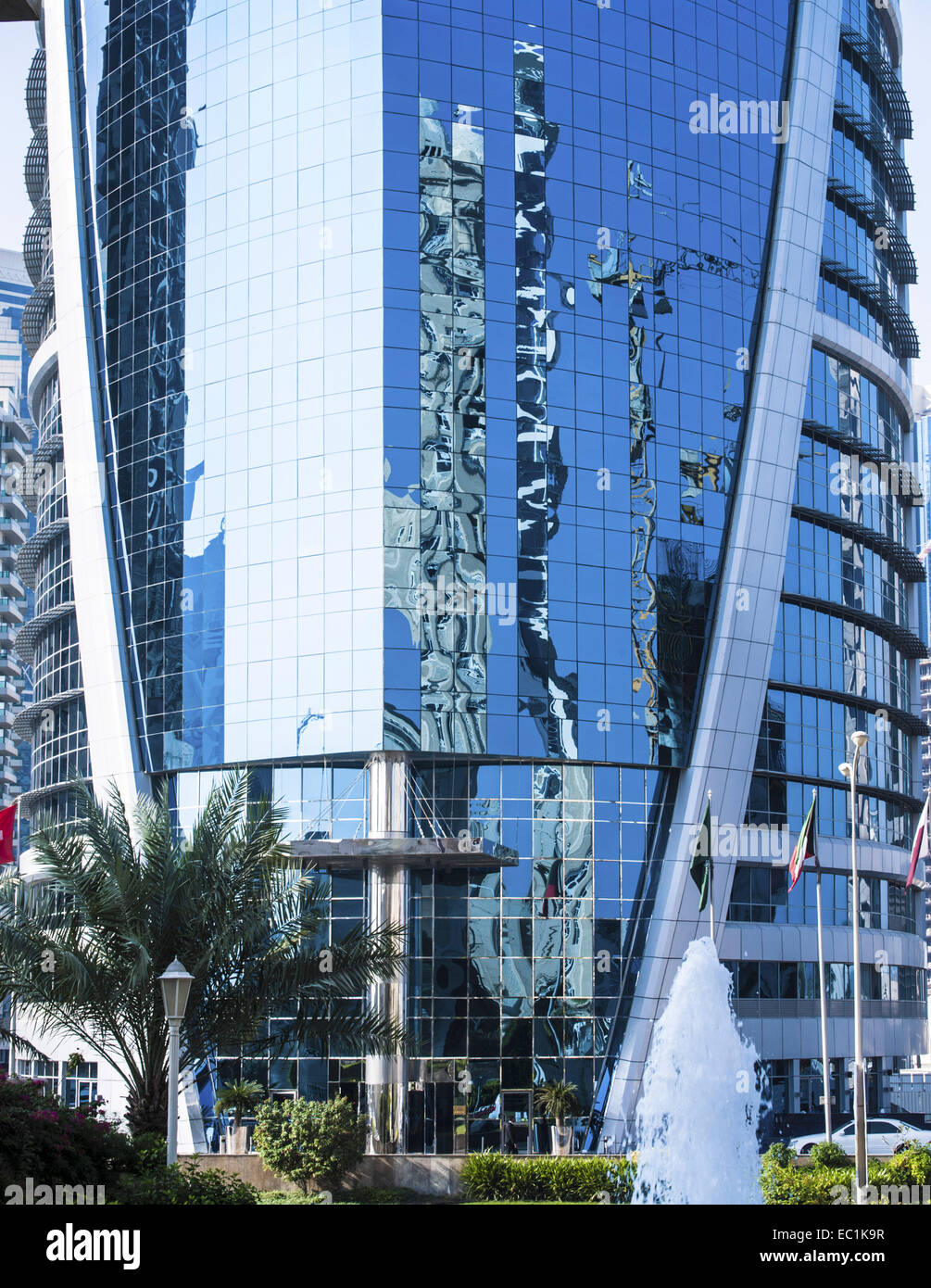 Blue glass construction with reflections of Sheraton, Doha Corniche - Stock Image