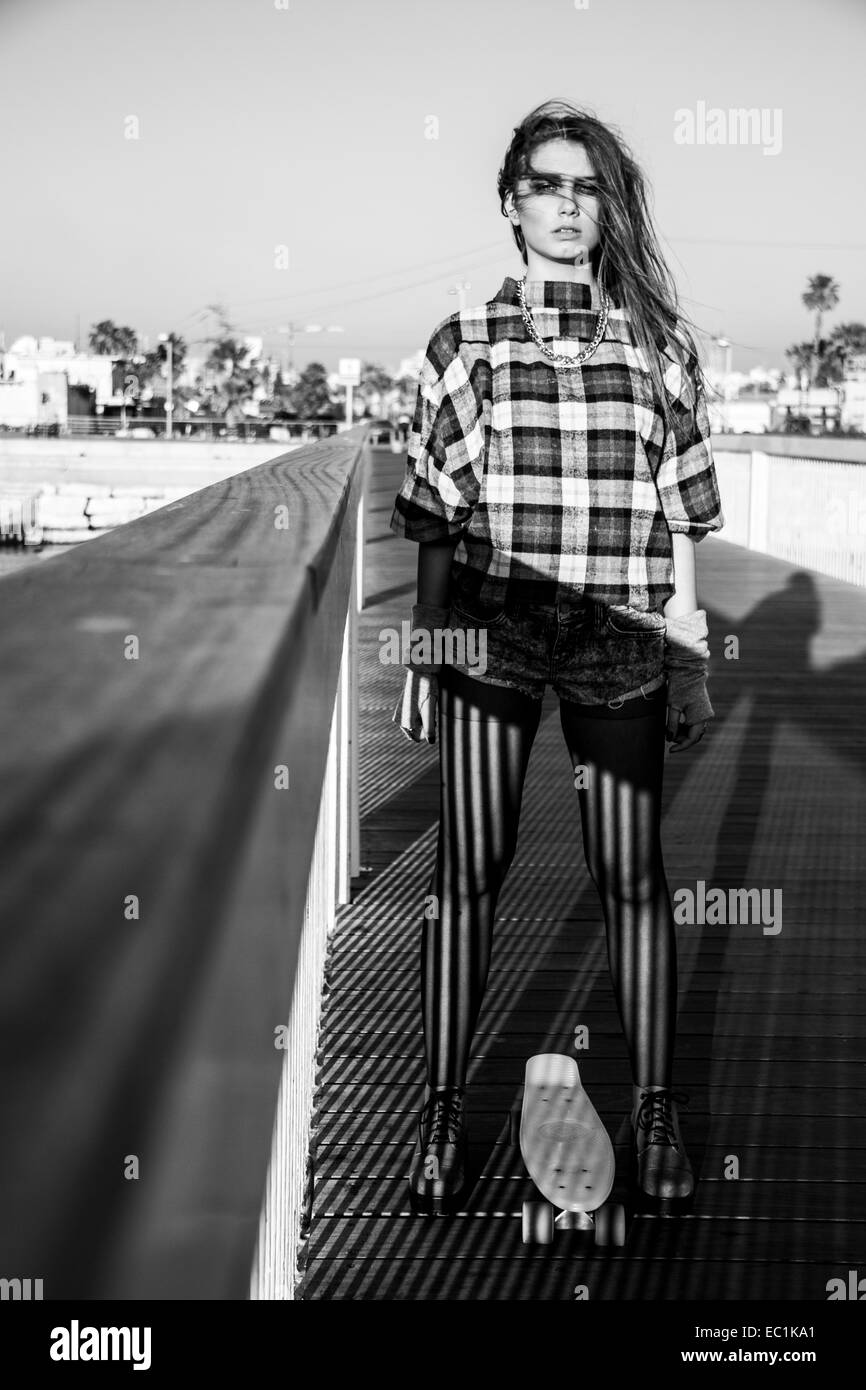 Young funky female Emo teen girl with skateboard - Stock Image