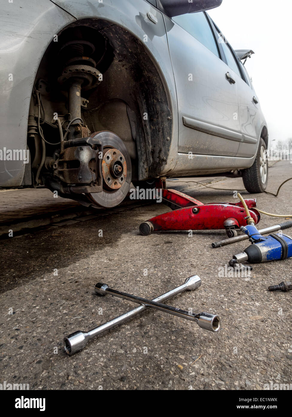 Passenger vehicle on lift with front tire removed - Stock Image