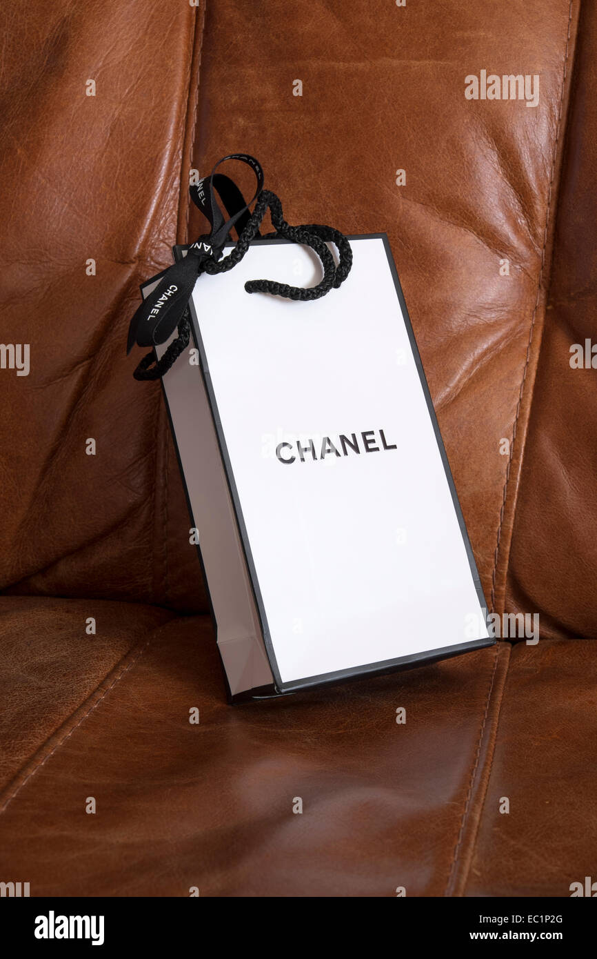 834da054fd15 black and white Chanel perfume gift wrapped carrier bag laying on a brown  leather chair -