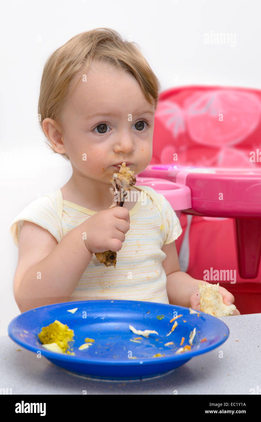 Portrait of a baby eating chicken meat and gets dirty - Stock Image