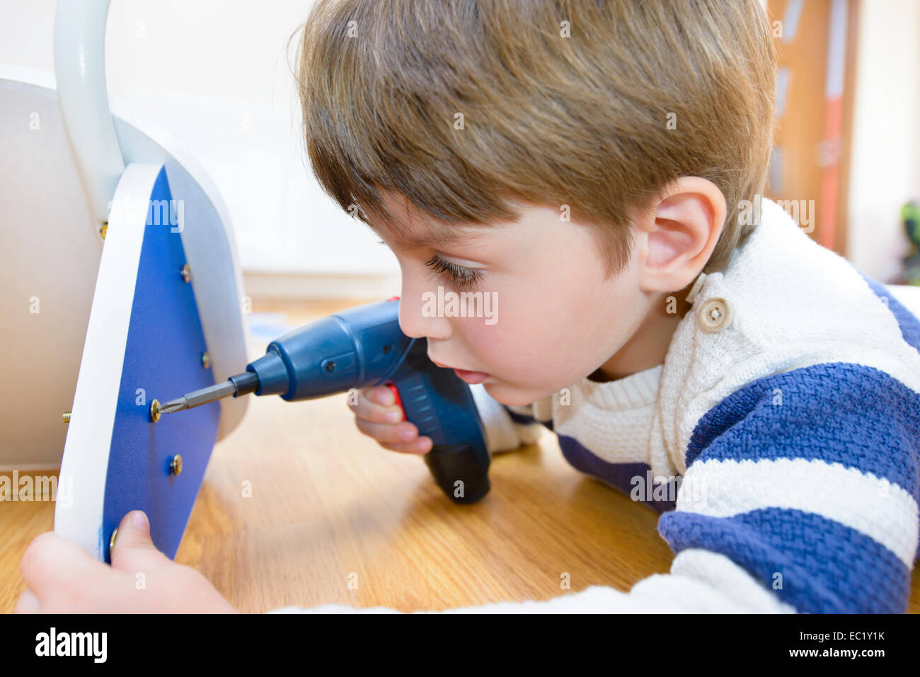 Little Boy using diy tool at home - Stock Image