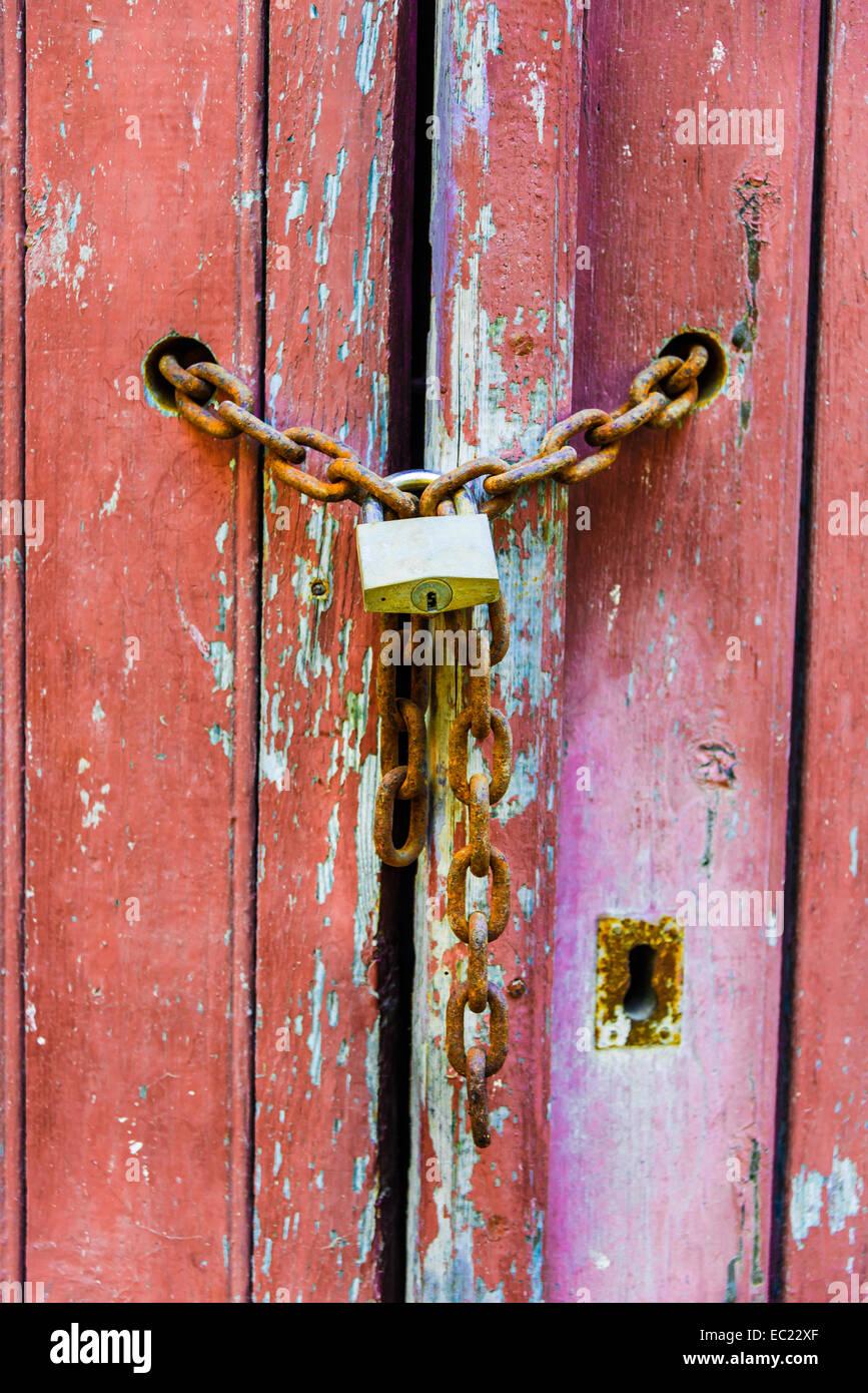 Lock on a chain, wood door - Stock Image