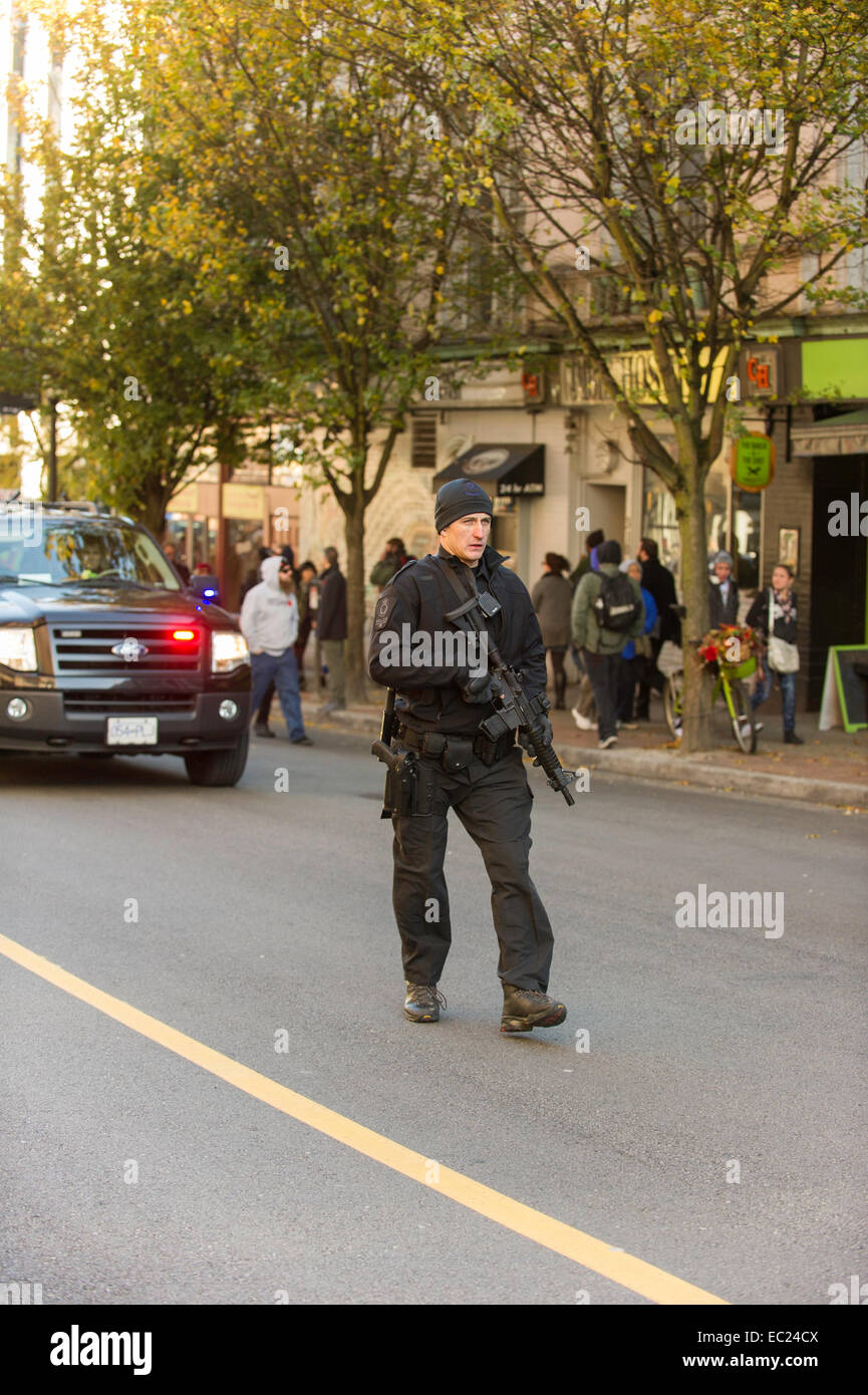 Heavily armed Vancouver city policeman walking down the center of the street - Stock Image