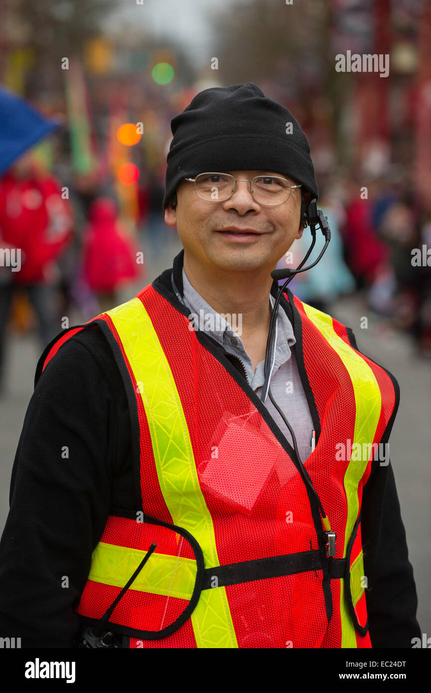 Asian man dressed in a high visibility safety vest during street event in Vancouver. - Stock Image