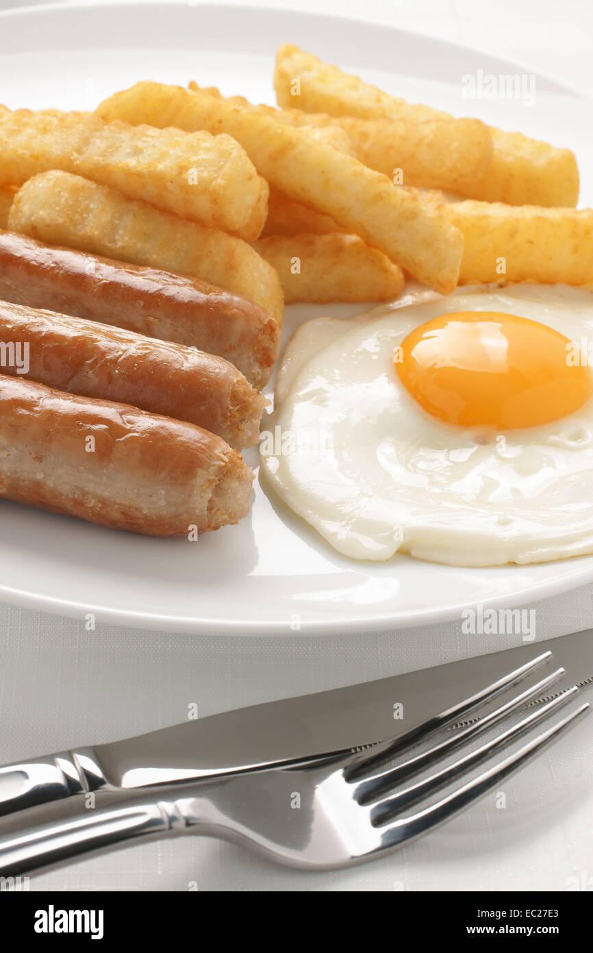 Sausage fried egg and chips a popular cafe menu item - Stock Image
