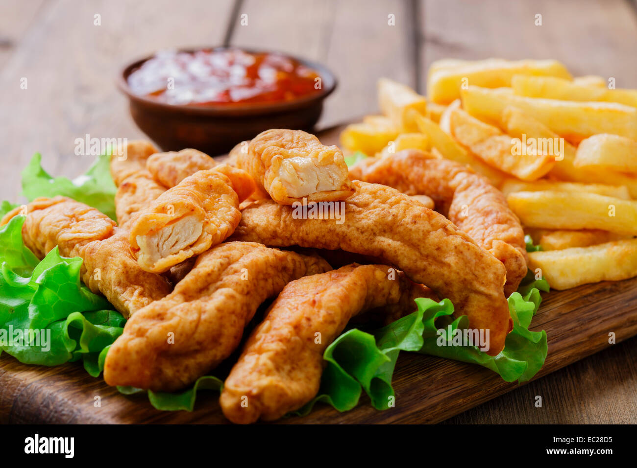 sticks breaded chicken with potatoes - Stock Image