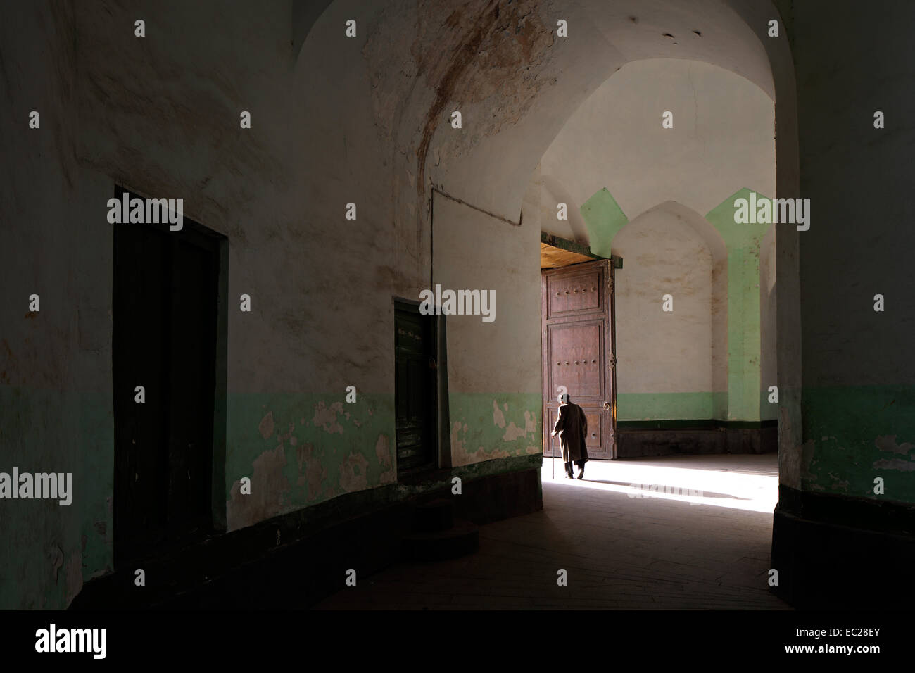 An old man leaves Id Kah Mosque, Kashgar, Xinjiang privince, China. This is the largest Mosque in China. Stock Photo