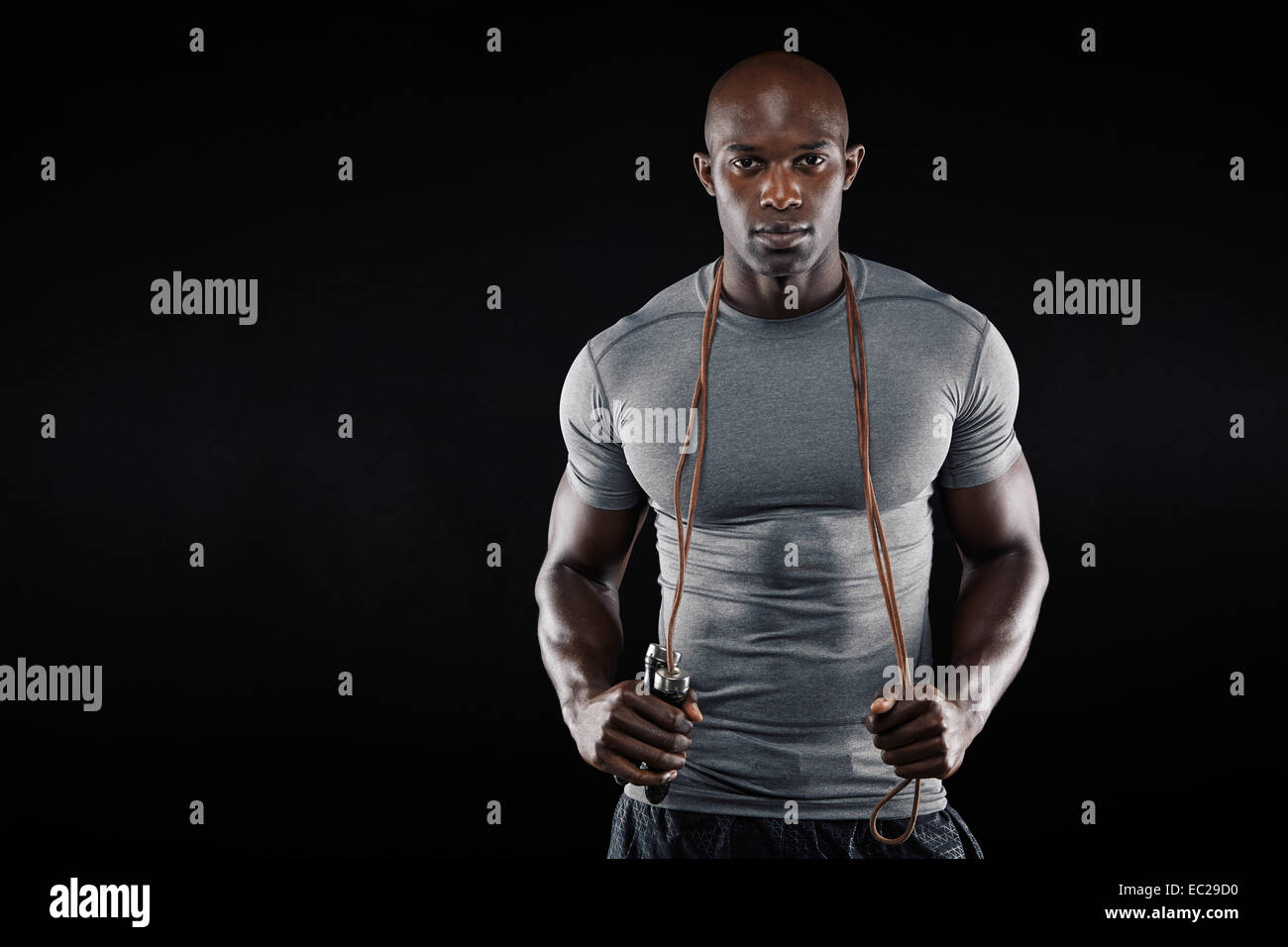 Handsome muscular man posing with jumping rope on black background. African fitness model with skipping rope. - Stock Image