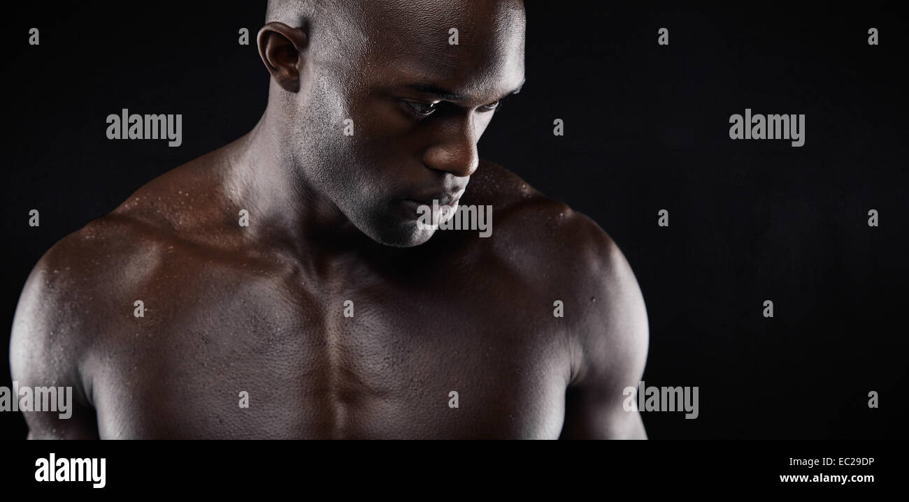 Close-up shot of shirtless African male model with muscular build on black background. Young man with muscular build. - Stock Image