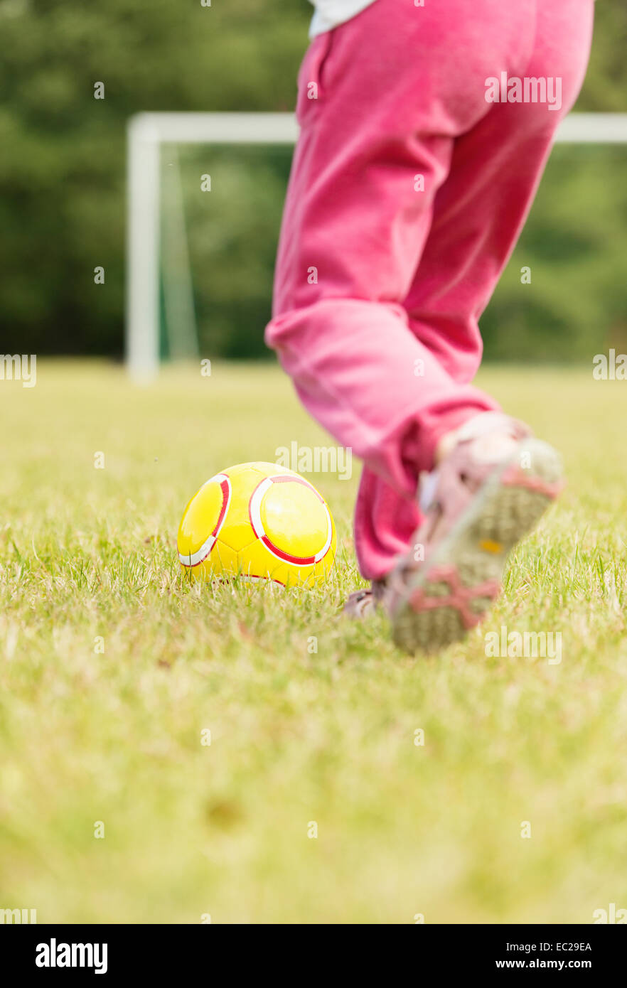 Girl in pink pants playing soccer, kicking a yellow football in front of goal. - Stock Image