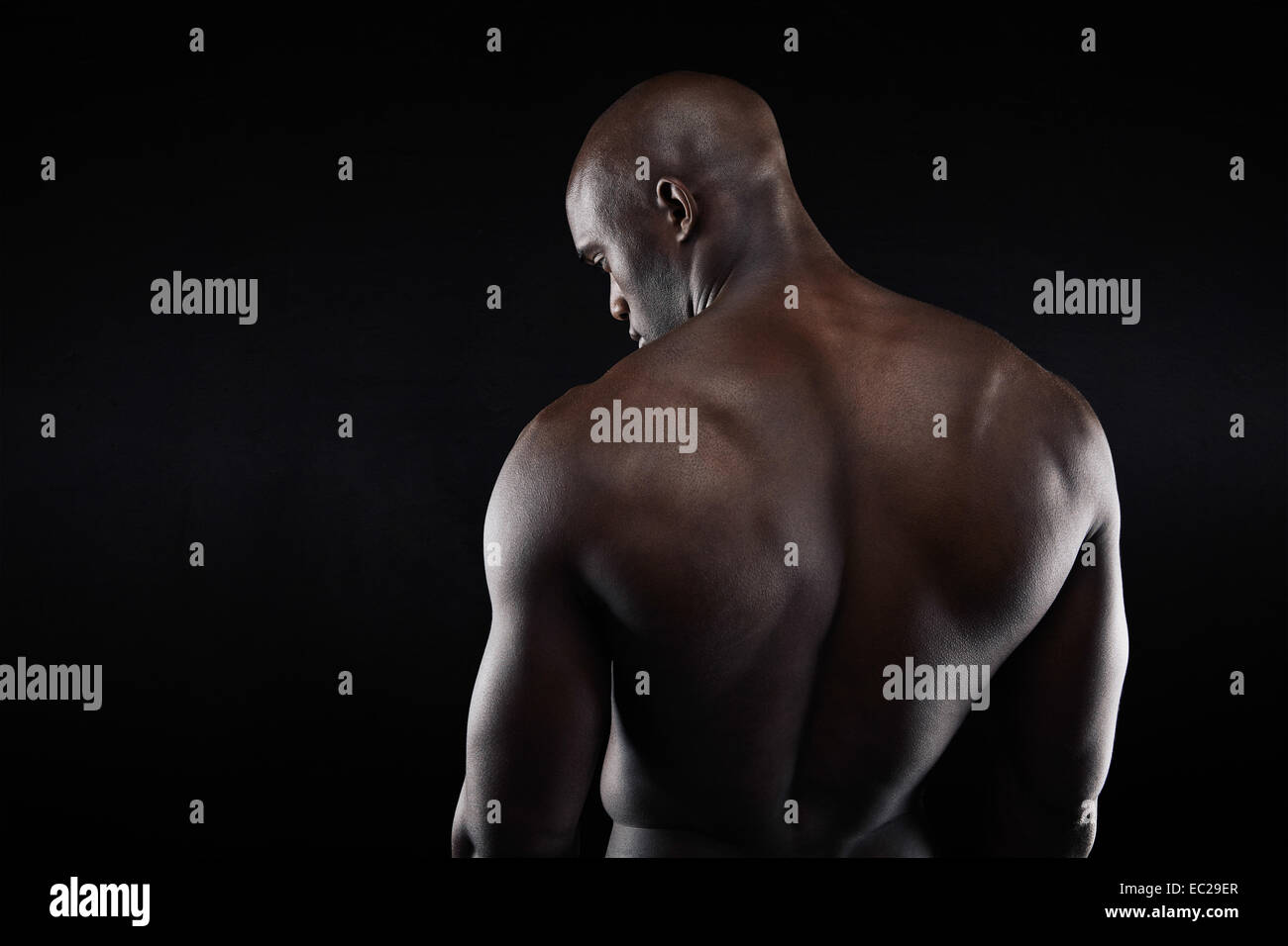 African muscular bodybuilder's back on black background. Shirtless fitness model with copyspace. - Stock Image