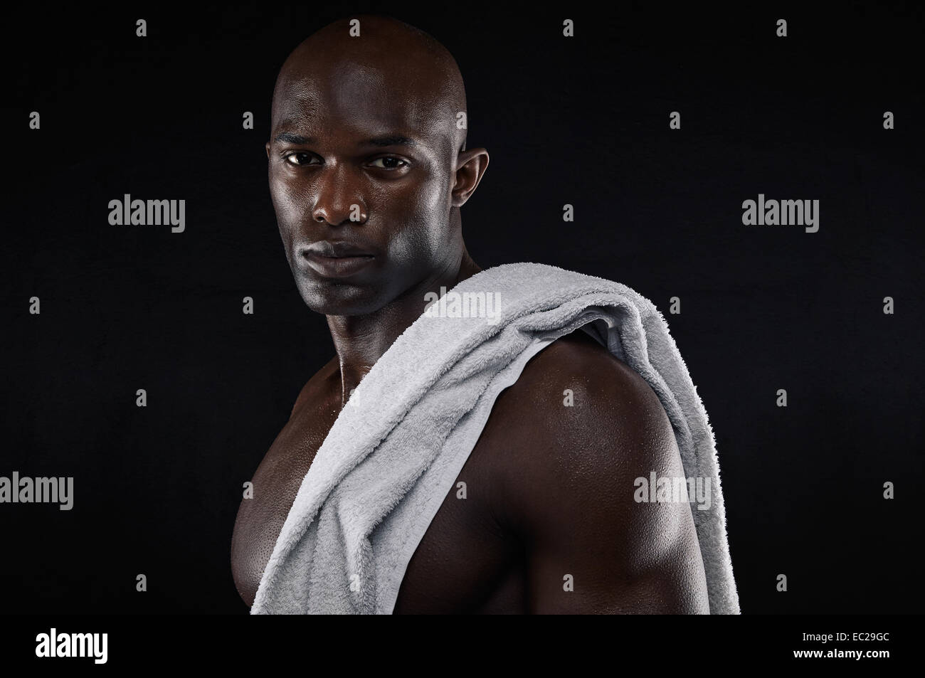 Portrait of strong young muscular man with a towel looking at camera on black background. Fit young African man - Stock Image