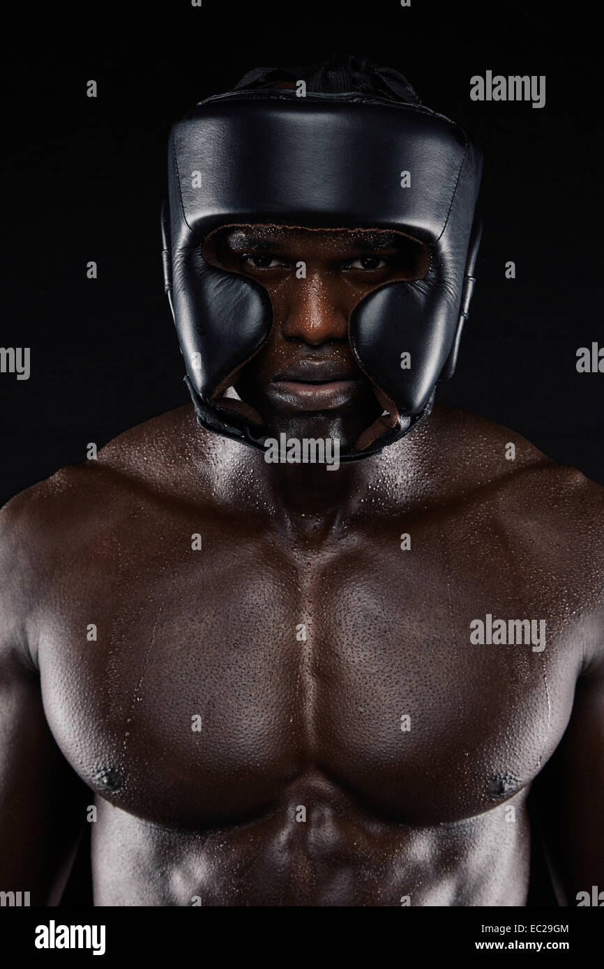 Portrait of African boxer wearing protective head guard against black background. Muscular man wearing boxing helmet. - Stock Image