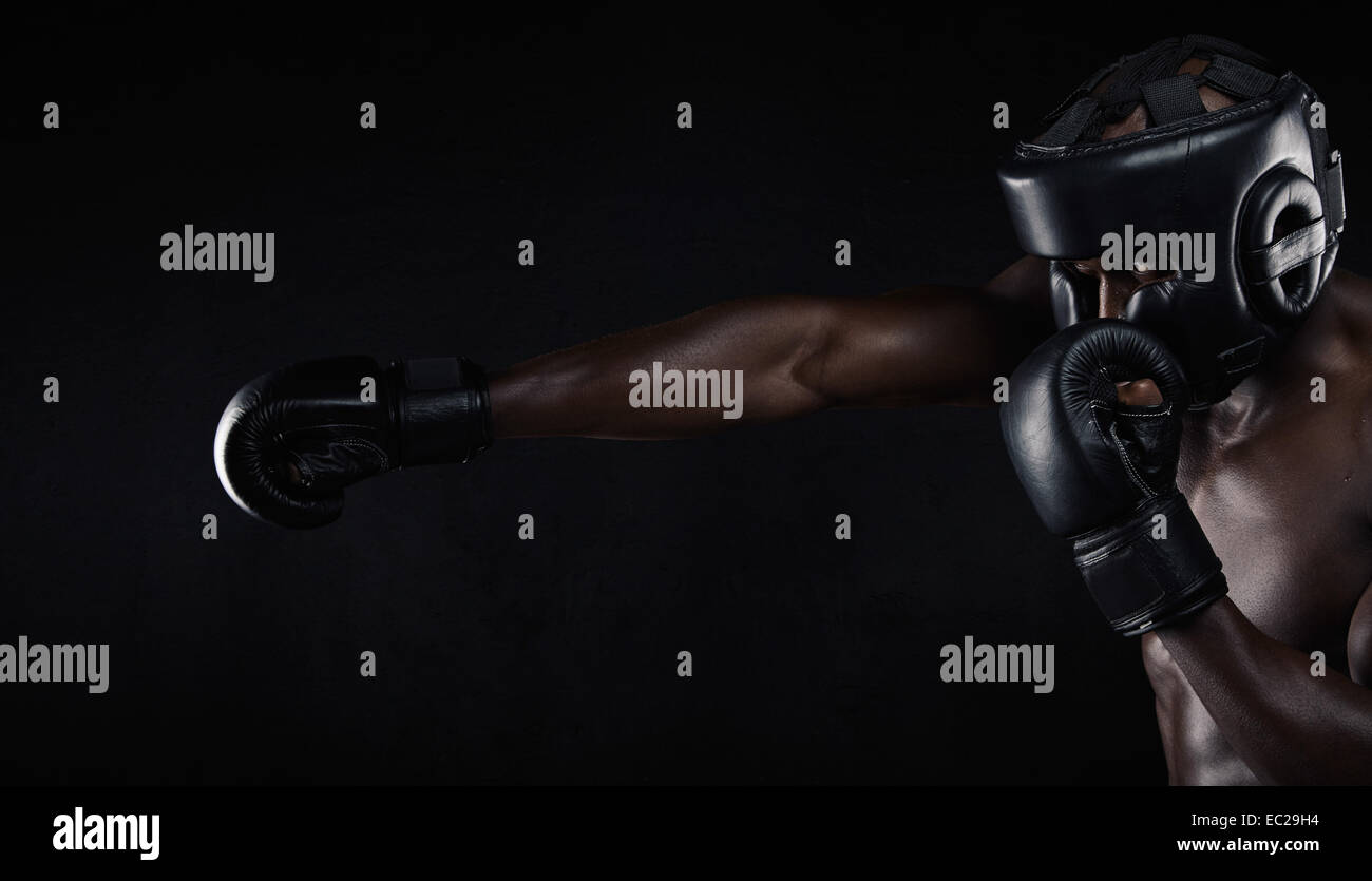 Image of African male boxer boxing against black background. Young man wearing protective head guard and boxing - Stock Image