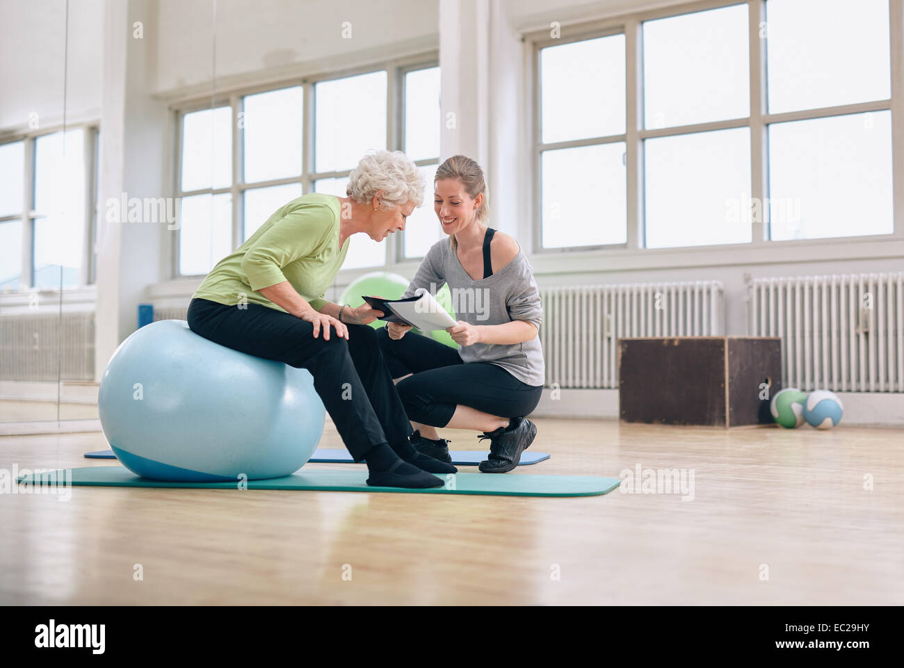 Elderly woman in a gym sitting on exercise ball and talking to her personal female trainer about exercise plan. - Stock Image