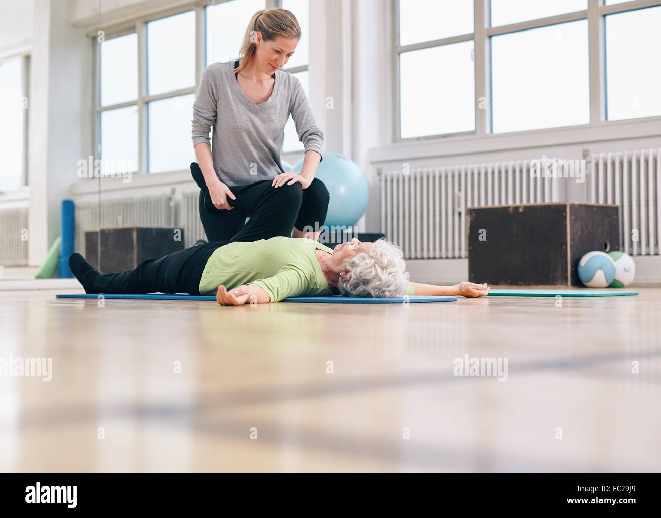 Female physical therapist assisting senior woman with leg exercise in therapy gym. Elder woman lying on floor being Stock Photo