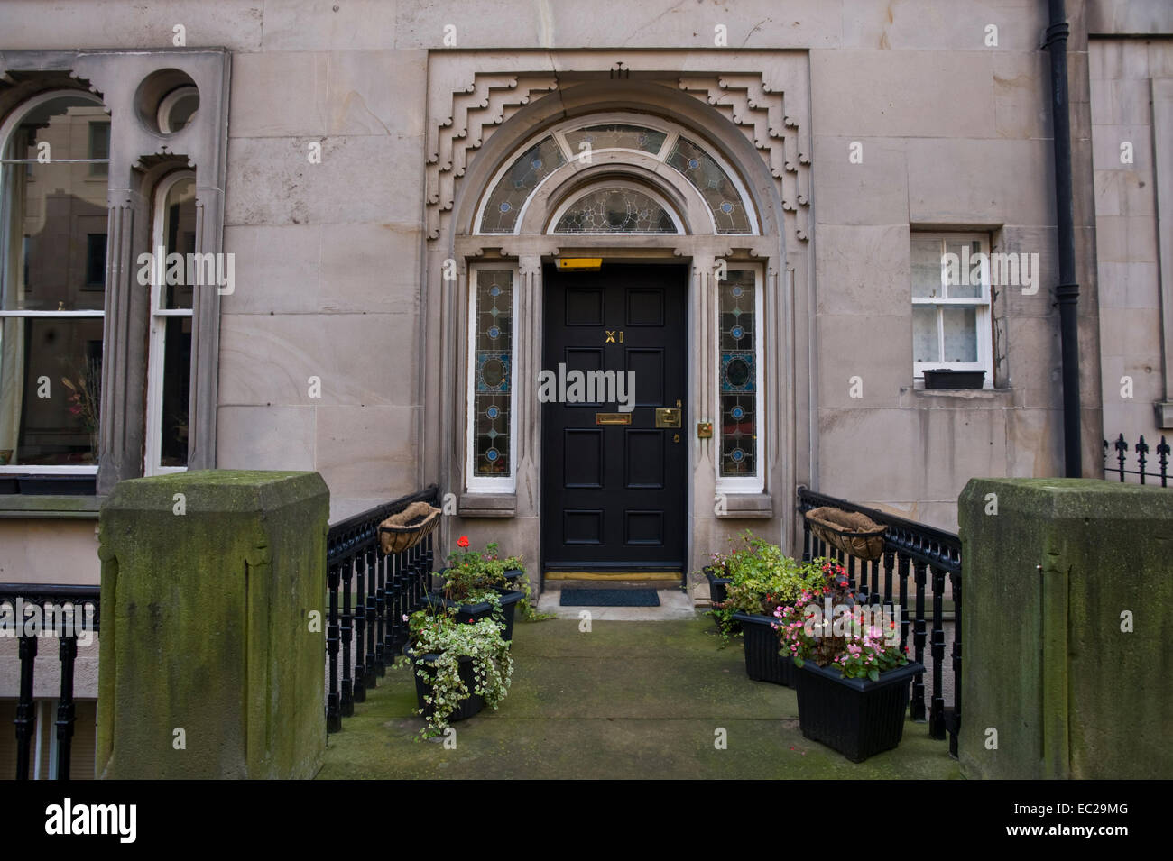 Black No XI front door with potted plants outside period house in ...