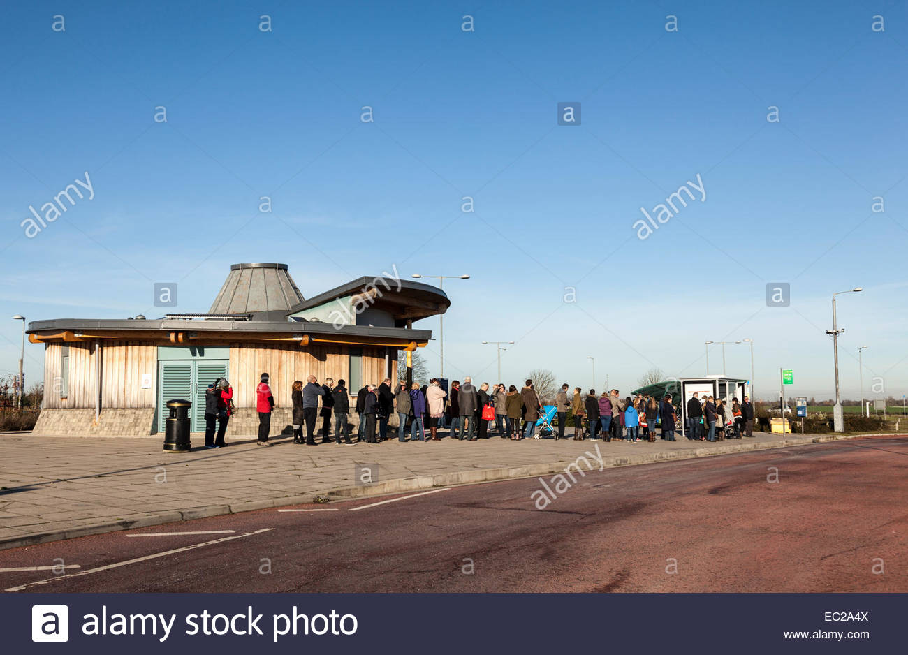 Passengers queueing for a bus at Milton Park and Ride, Cambridge, UK Stock Photo