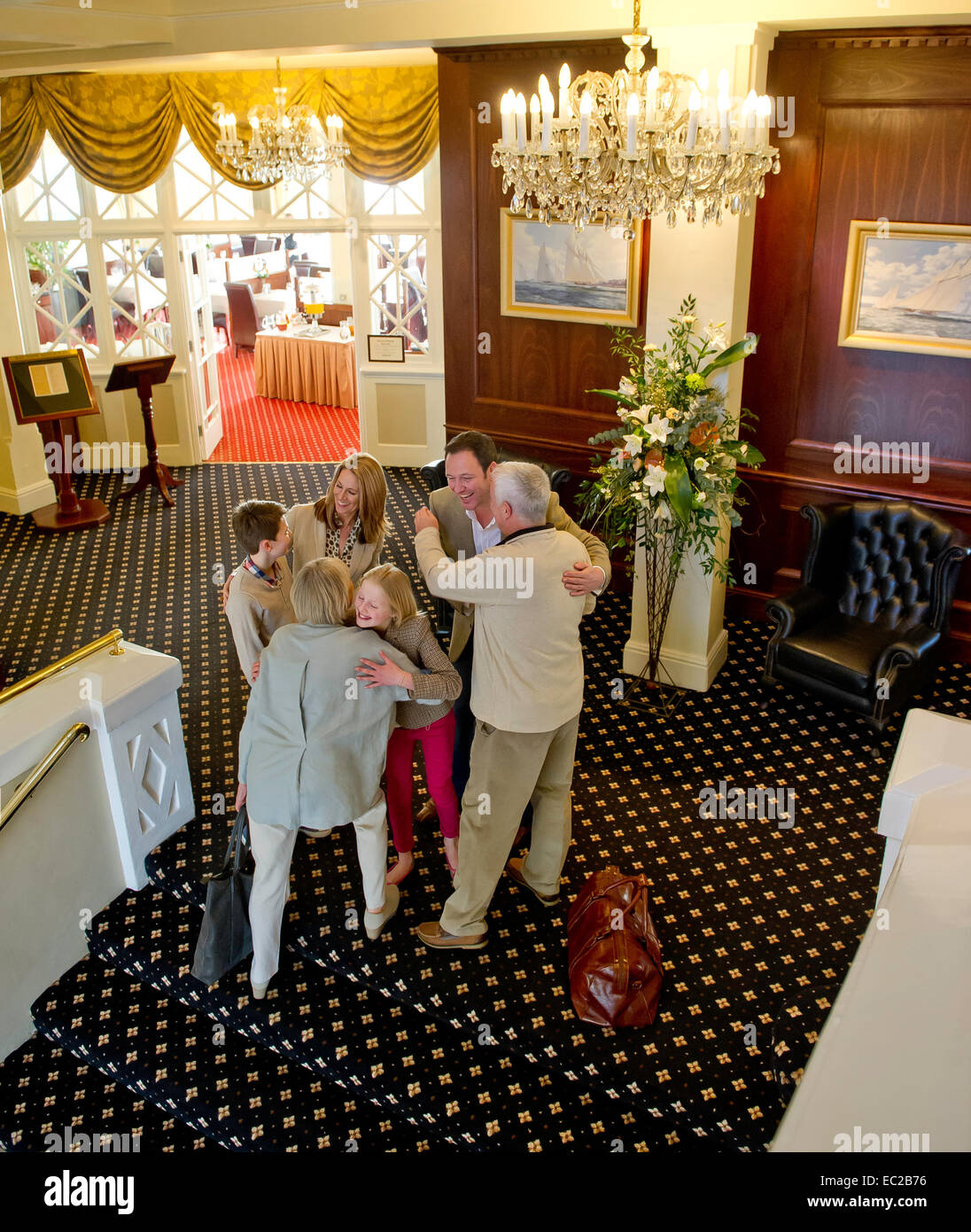 An extended family meeting up in a hotel lobby England UK - Stock Image