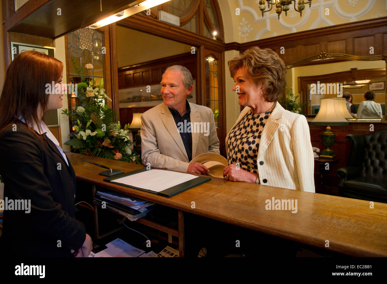 An older couple checking into a hotel - Stock Image