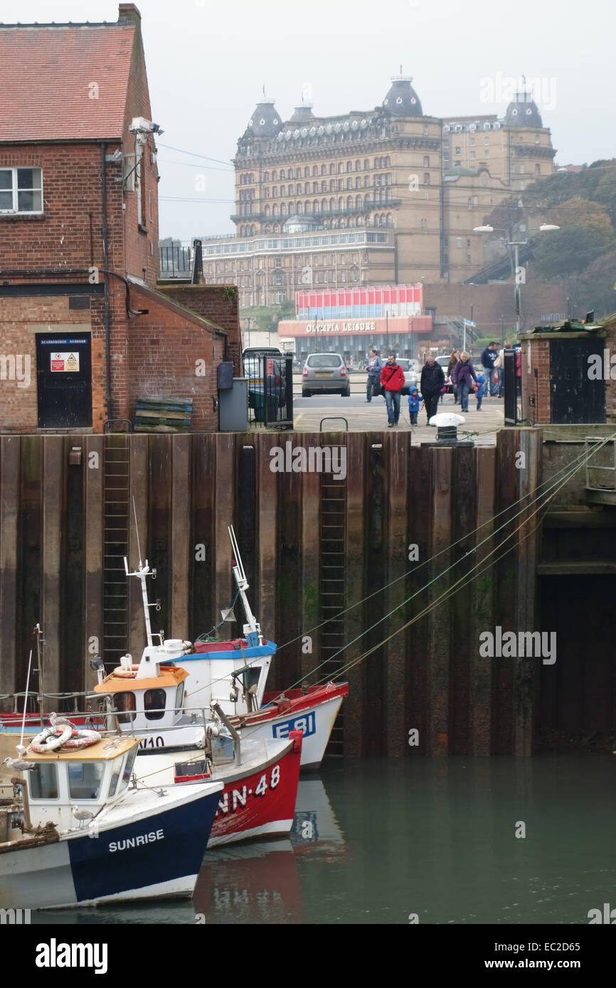 View of the Grand Hotel through buildings surrounding the harbour and fishing boats in Scarborough, North Yorkshire - Stock Image