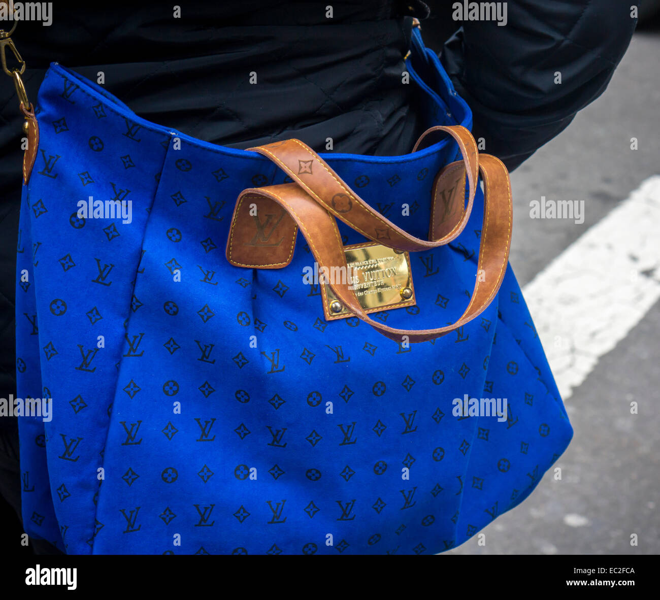 78f5cbbfd8a6 A woman carries a handbag with a Louis Vuitton label in New York on  Thursday