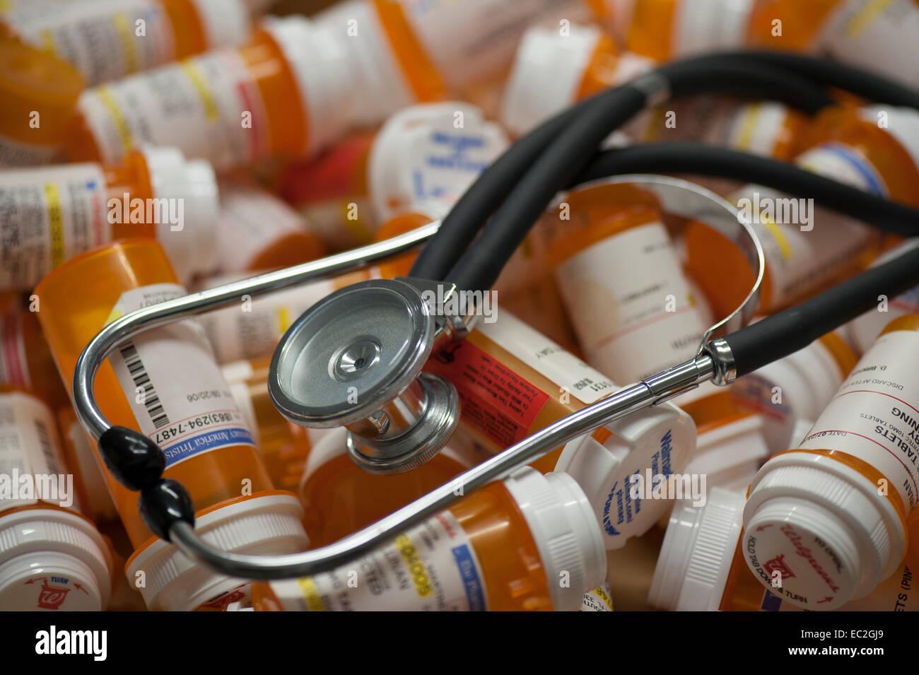 stethoscope lying on pile of prescription bottles - Stock Image
