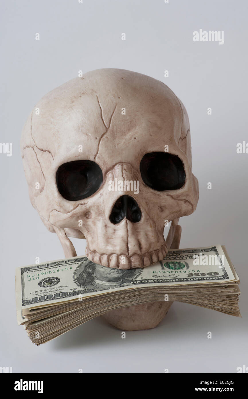 human skull with $100 dollar bills stuffed in mouth - Stock Image