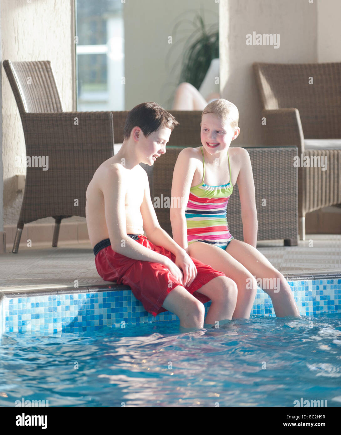 A Boy And Girl Sat By A Swimming Pool Indoors With Sun Shining Stock Photo 76274851 Alamy