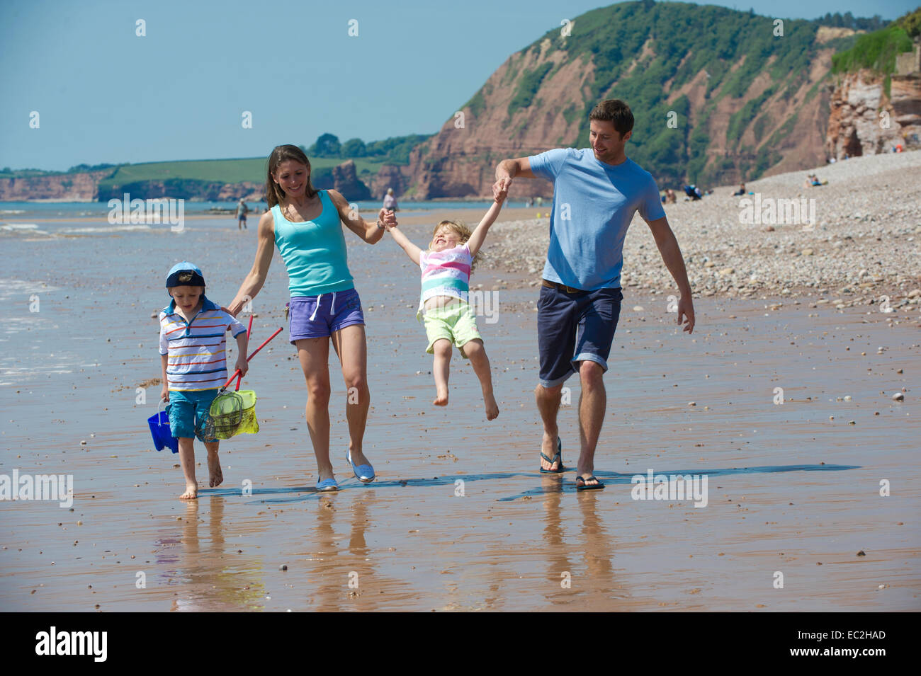 Family on the beach at Sidmouth on holiday having fun - Stock Image